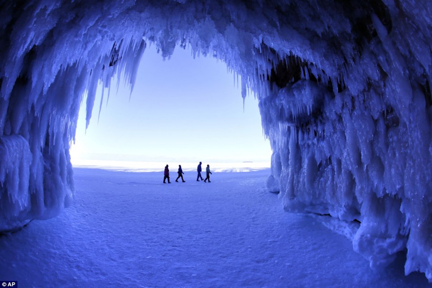 People walking within ice cave