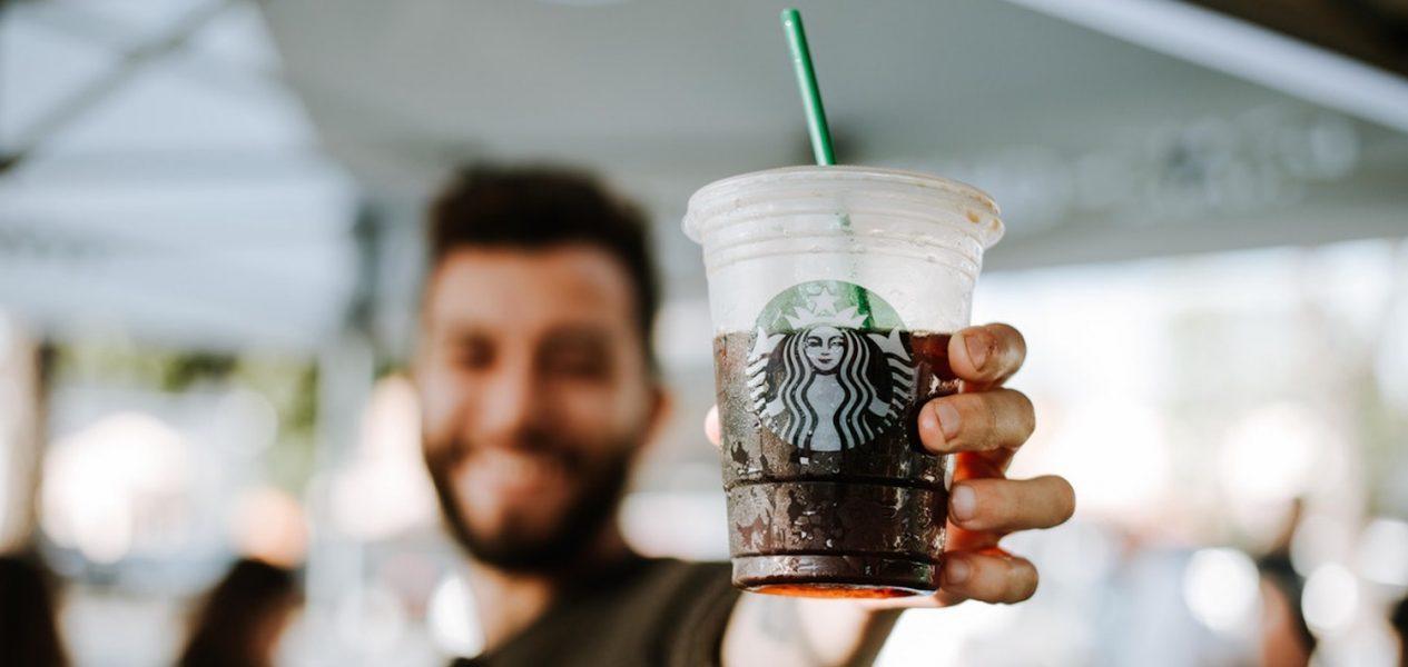 guy holding starbucks coffee