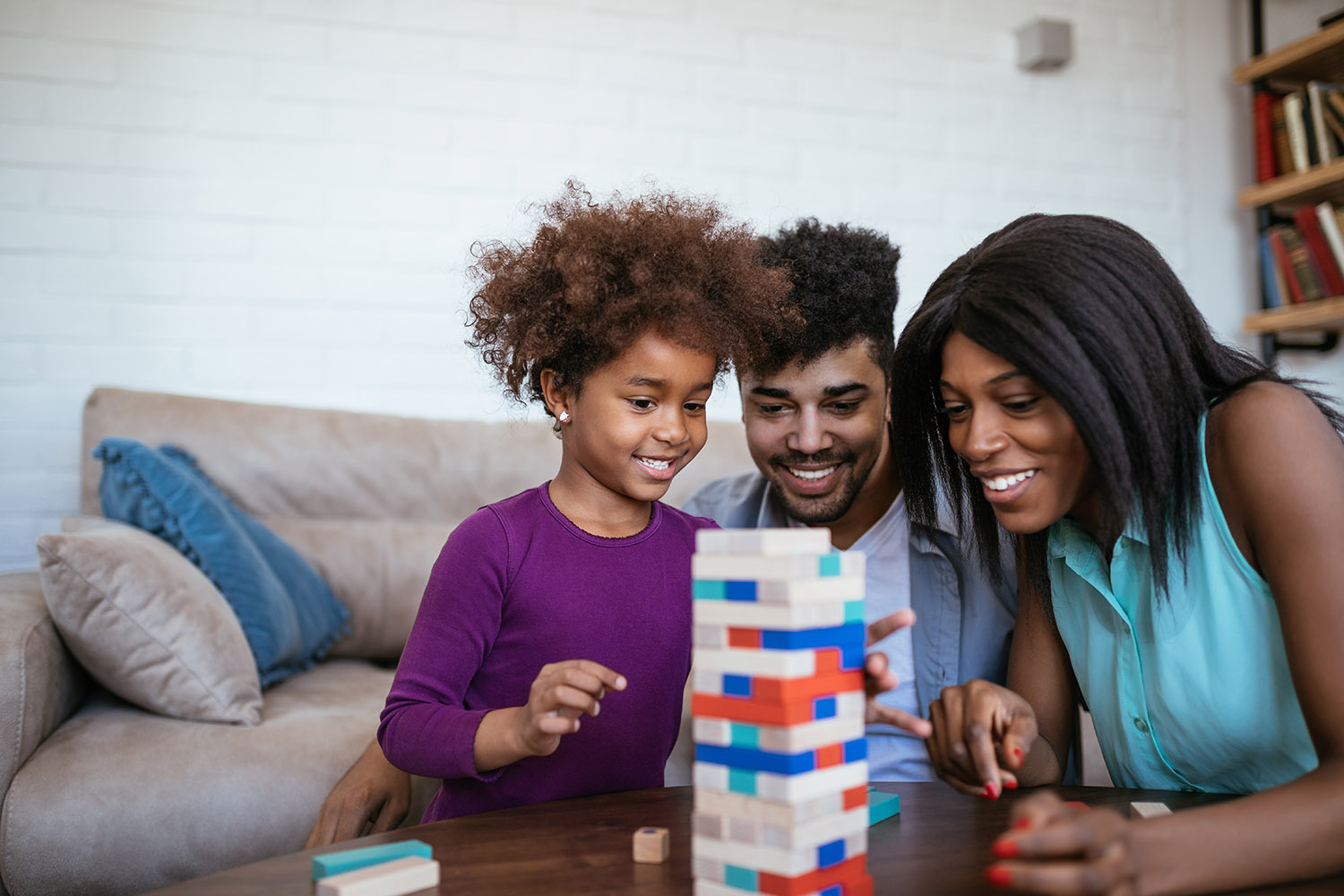 black family with young girl playing jenga kids gift guide